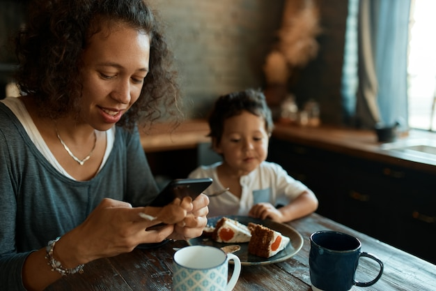 Madre soltera joven ocupada que usa el teléfono celular para el trabajo a distancia, escribiendo publicaciones en cuentas de redes sociales
