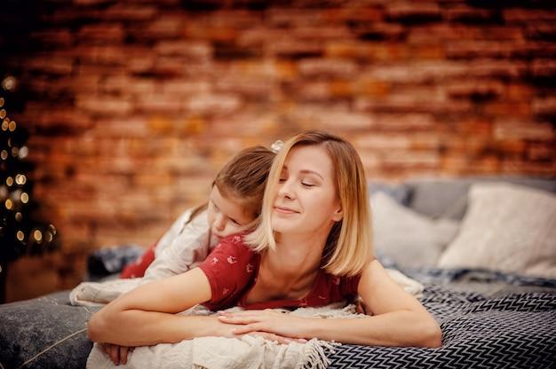 Madre sonriente de cabello rubio con hija triste en la espalda en pijama rojo acostado en la cama gris mirando hacia los lados frente a la pared de ladrillo marrón y el árbol de navidad con luces de guirnalda