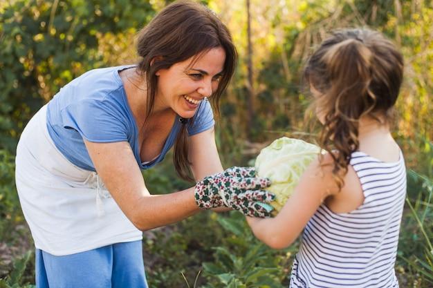 Madre sonriente dando repollo a su hija