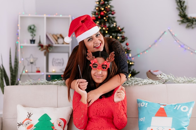 Madre sonriente con gorro de papá noel abraza a su hija con gafas de reno sosteniendo bengalas sentado en el sofá disfrutando de la navidad en casa
