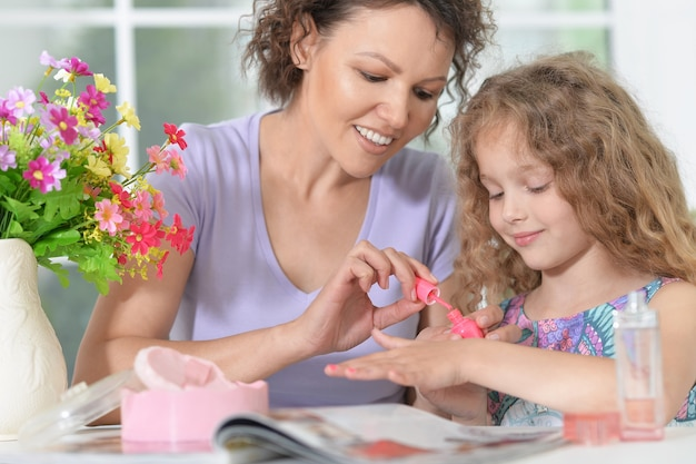 Madre sonriente con hija pequeña con revista en casa