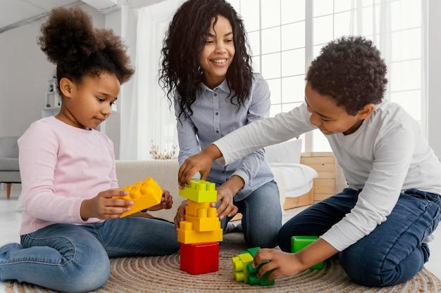 Madre sonriente jugando en casa con sus hijos