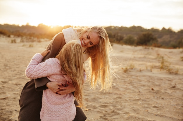 Madre sonriente jugando con su pequeña hija