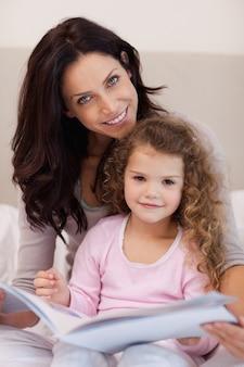 Madre sonriente leyendo un cuento antes de dormir con su pequeña hija