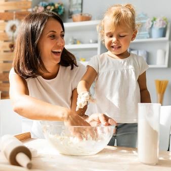 Madre sonriente y linda hija preparando masa