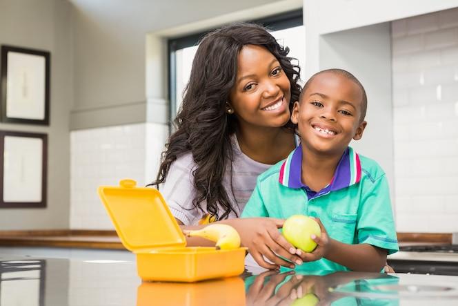 Madre sonriente preparando el almuerzo escolar de hijos