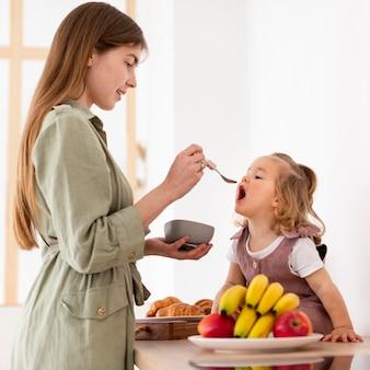 Madre sonriente que alimenta a la hija