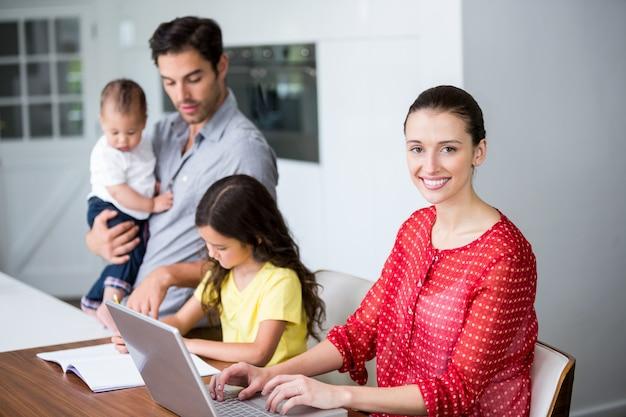 Madre sonriente que trabaja en la computadora portátil con el padre ayudando a la hija en la tarea