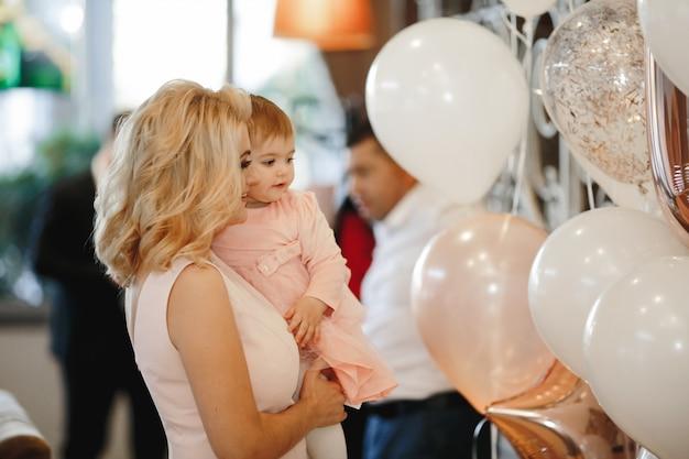 La madre sonriente sostiene a su pequeña hija linda