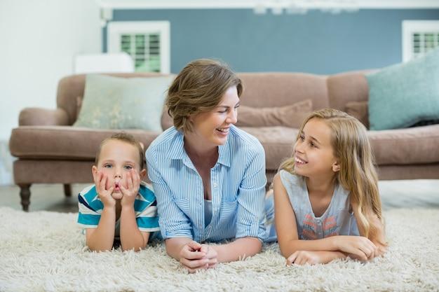 Madre sonriente con su hijo e hija acostada sobre una alfombra en la sala de estar