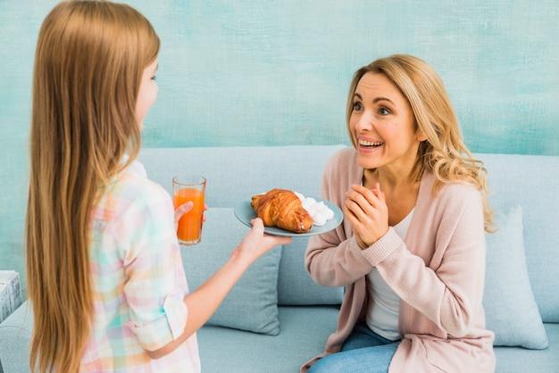 Madre sorprendida mirando a su hija con jugo y croissant