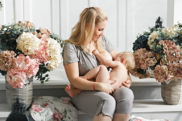 Madre sosteniendo al bebé en su regazo antes de amamantar. estudio de tiro en la decoración de flores