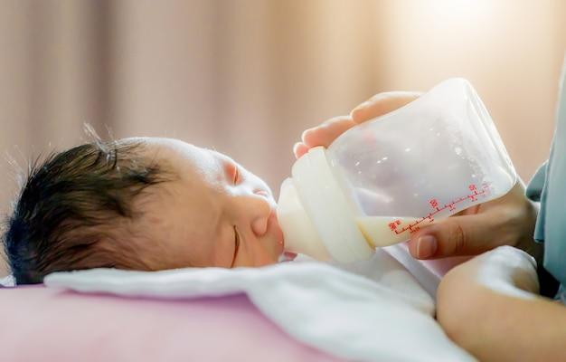 Madre sosteniendo y alimentando al bebé recién nacido de la botella de leche, concepto de amor