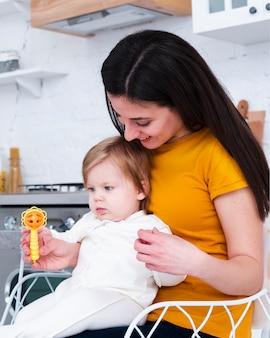 Madre sosteniendo bebé jugando con juguete