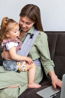 Madre sosteniendo niño y trabajando