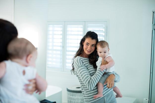 Madre sosteniendo a su bebé y mirando el espejo en casa
