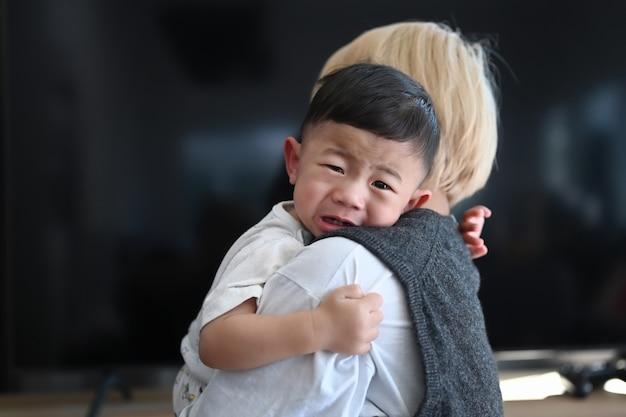 Madre sosteniendo a su hijo llorando sala de estar en casa.