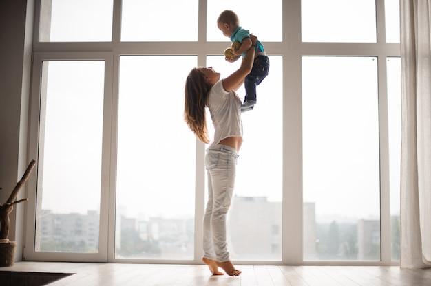 Madre sosteniendo a su niño en el aire