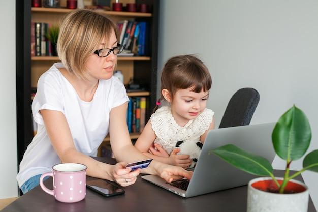 Madre sosteniendo una tarjeta de crédito con su pequeña hija sentada cerca mirando la computadora portátil