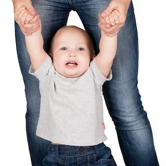 La madre sostiene al bebé de las manos sobre fondo blanco.