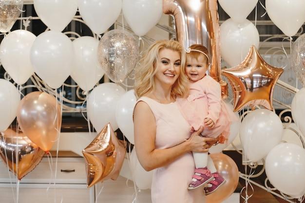 La madre sostiene a su pequeña hija linda en los globos