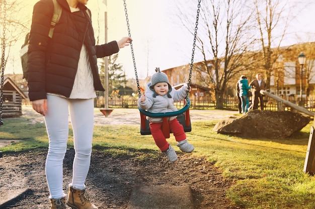 Madre con su bebé vestido con ropa de abrigo caminando en un día soleado al aire libre