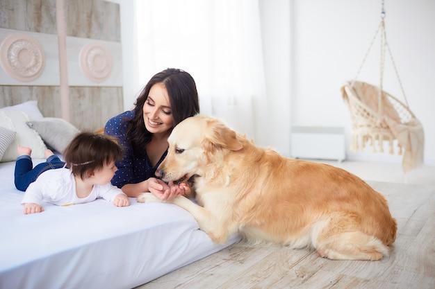 La madre con su hija se acuesta en la cama y el perro los mira