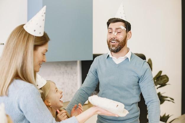 La madre y su hija celebran el cumpleaños del padre en la cocina la madre golpea un pastel en la cara del hombre