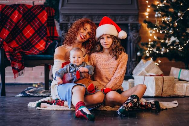 Madre con su hija e hijo en navidad por arbol de navidad