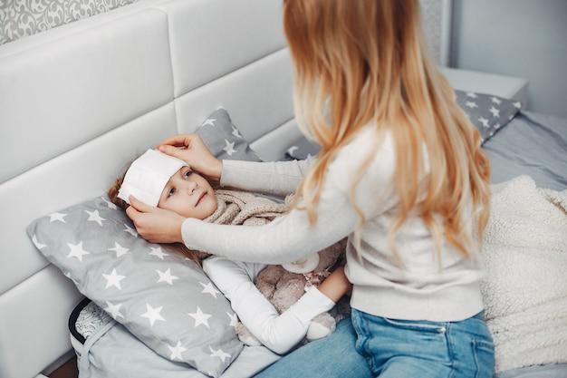 Madre con su hija illnes en un dormitorio