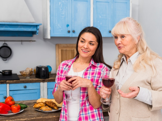Madre y su hija joven de pie en la cocina con copas de vino en las manos