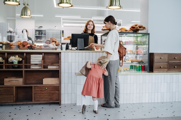 Madre con su hija pagando pasteles en una panadería. la niña es muy inquieta e impaciente.