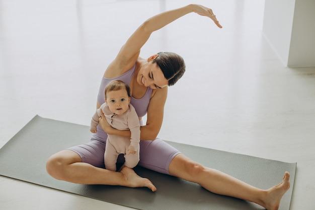 Madre con su hija practicar yoga en casa