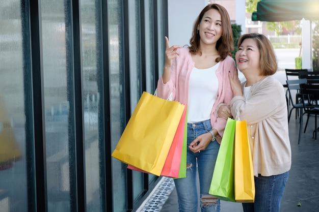 Madre con su hija sosteniendo bolsas de compras en los grandes almacenes, familia feliz y concepto de personas.