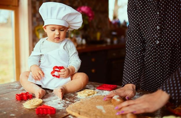 La madre con su hijo amasa la masa en la cocina