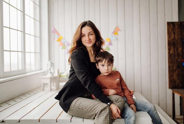 Madre y su hijo están posando en el estudio y vistiendo ropa informal.