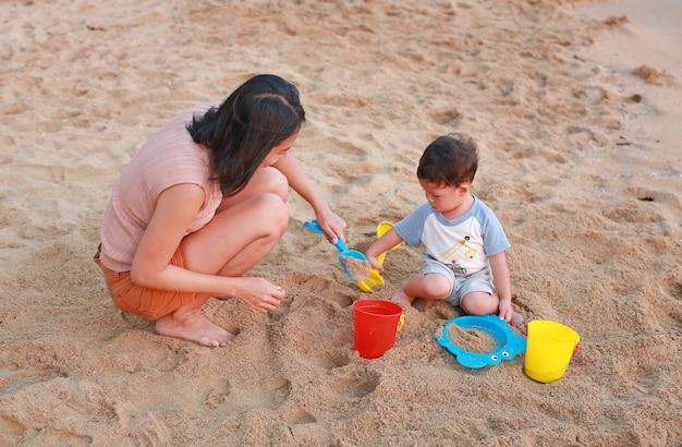 Madre y su hijo jugando arena en la playa con juguete de plástico