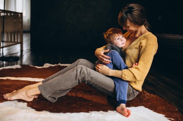 Madre con su hijo jugando en la habitación.