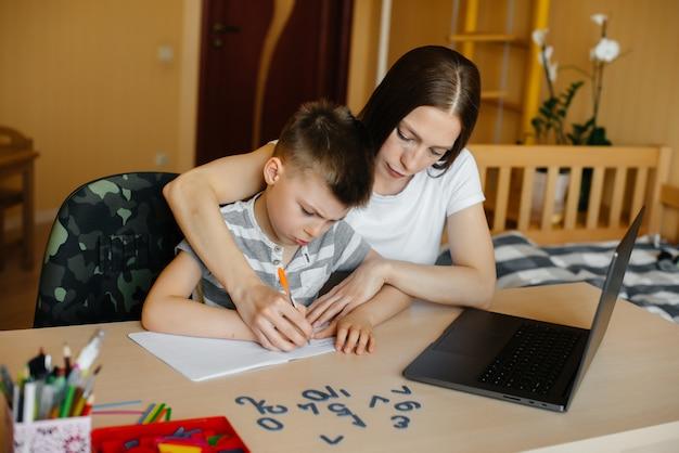 Una madre y su hijo participan en el aprendizaje a distancia en casa frente a la computadora. quédate en casa, entrenando.