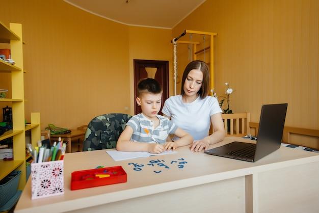 Una madre y su hijo participan en el aprendizaje a distancia en casa frente a la computadora.