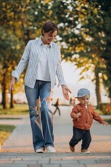 Madre con su hijo pequeño en el parque otoñal