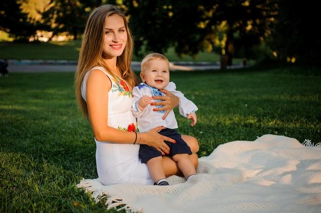 Madre y su hijo pequeño vestidos con las tradicionales camisas bordadas sentados en la tela escocesa en el parque