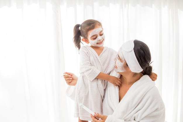 Madre y su joven bonita hija divirtiéndose en el dormitorio y haciendo máscaras faciales de arcilla