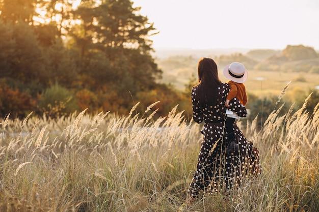 Madre con su niña en un campo de otoño