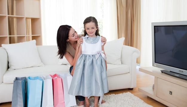 Madre y su niña probándose un vestido después de ir de compras