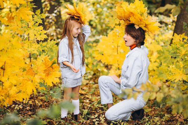 Madre con su pequeña hija en un bosque lleno de hojas doradas