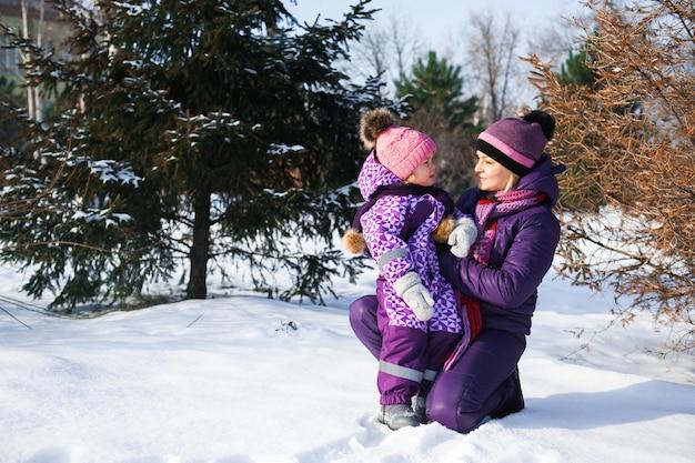 Madre y su pequeña hija disfrutando hermoso día de invierno al aire libre.