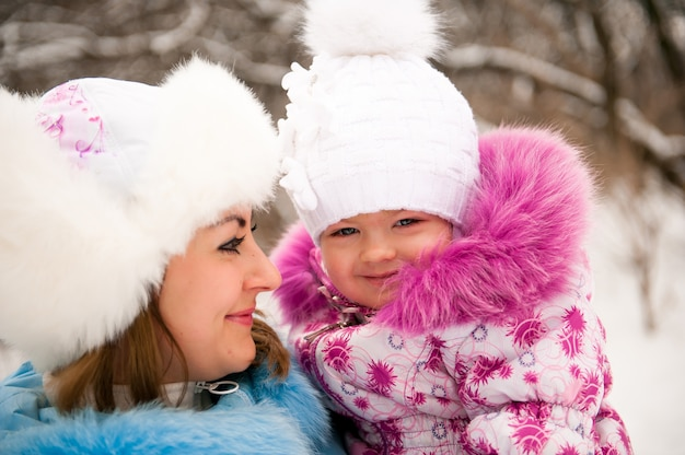 Madre y su pequeña hija disfrutando hermoso día de invierno