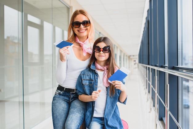 Madre y su pequeña hija con equipaje en el aeropuerto.