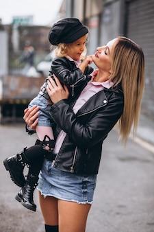 Madre con su pequeña hija fuera de la calle